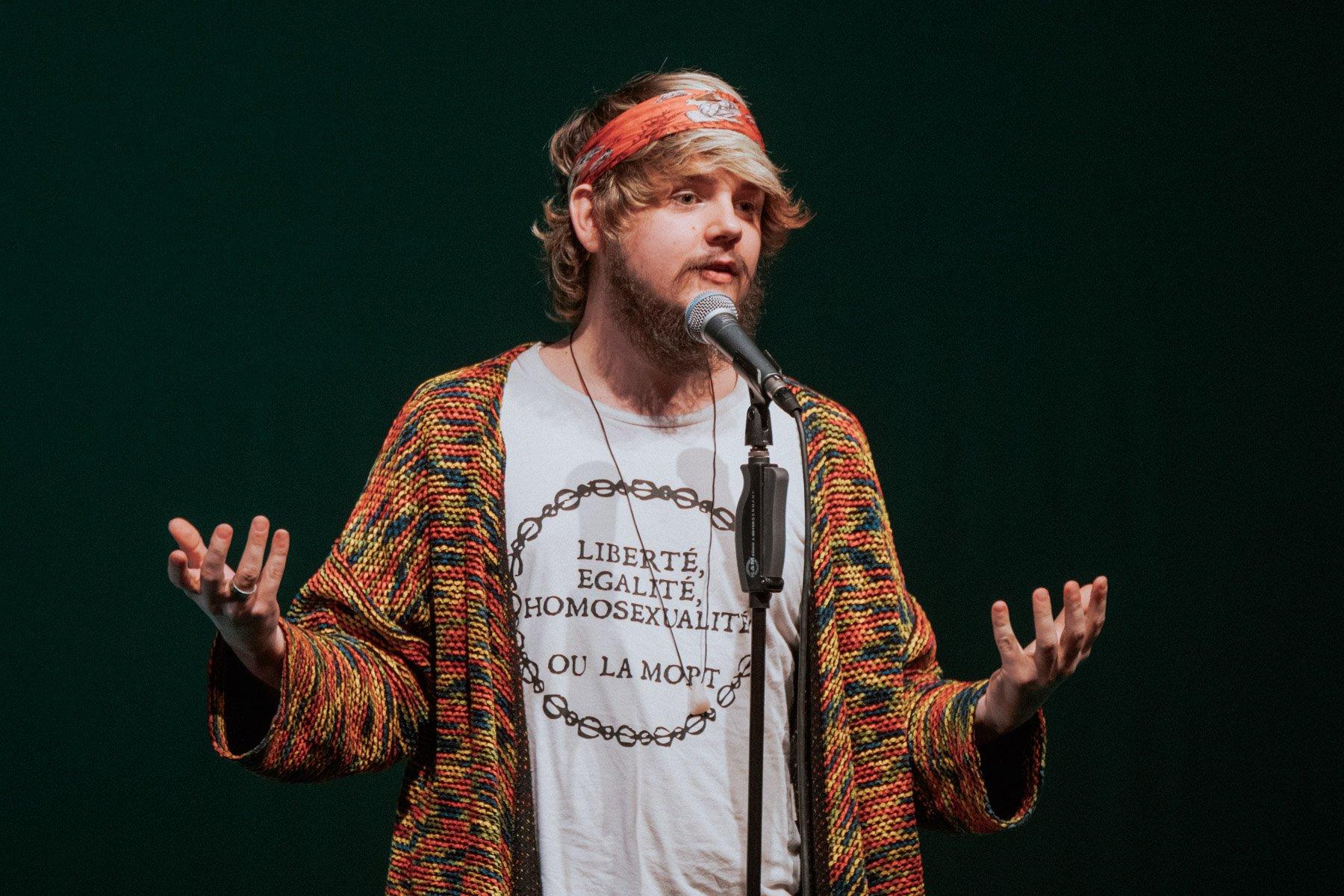 Sven Hensel spricht in ein Mikrofon. Auf seinem T-Shirt steht auf französisch: Liberté. Egalité. Homosexualité. Ou la Mort.