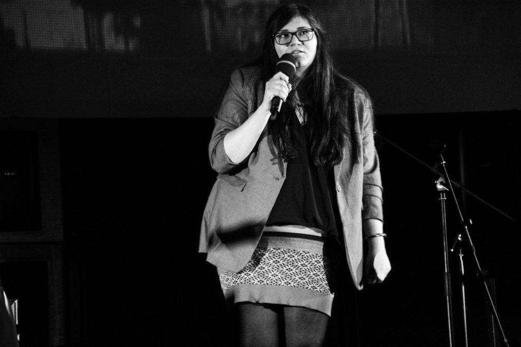 Stefanie Menschner steht auf einer Bühne. In der rechten Hand hält sie ein Mikrofon.