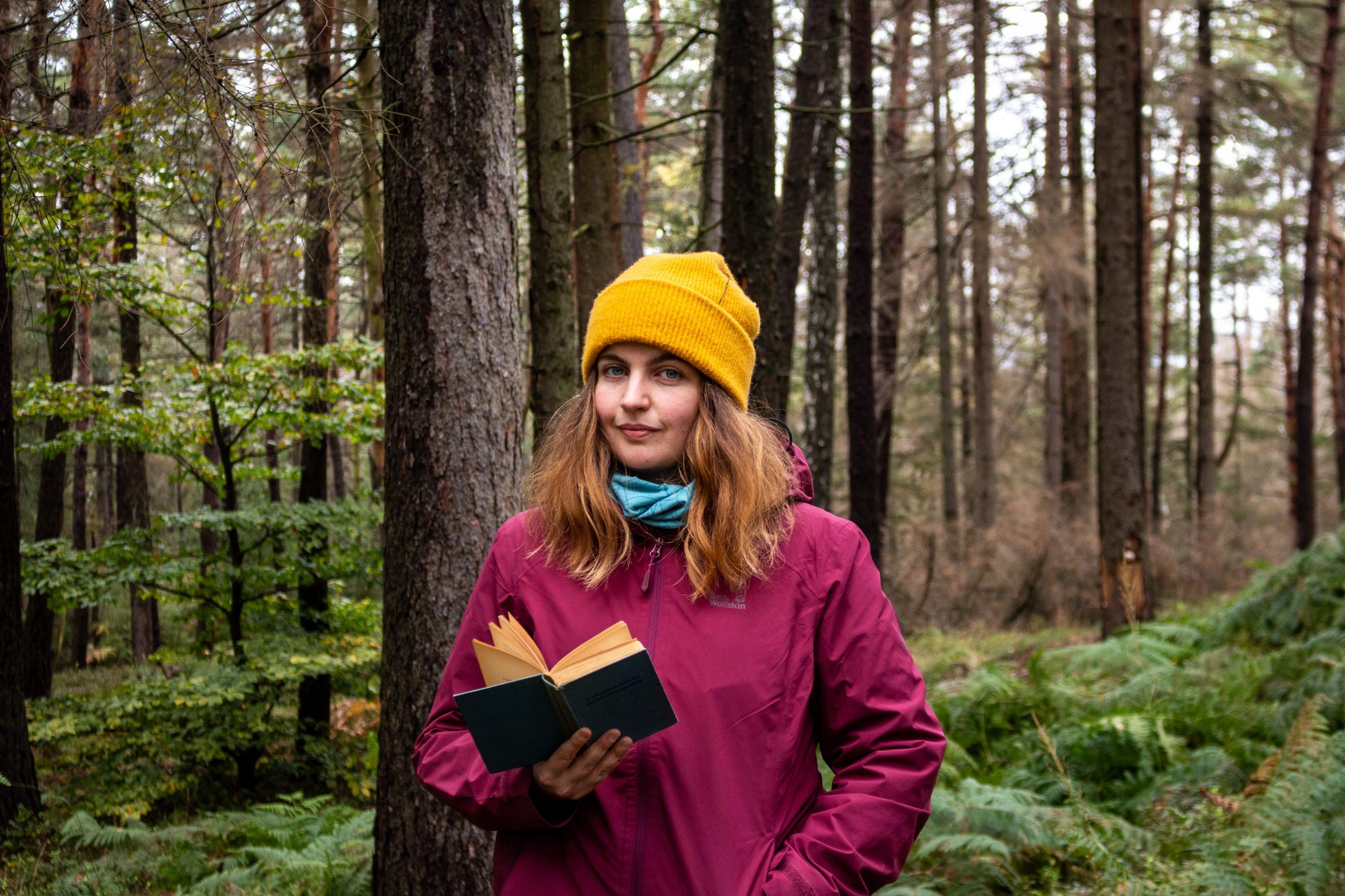 Marsha Richarz steht in einem Wald. In ihrer rechten Hand hält sie ein altes Buch.