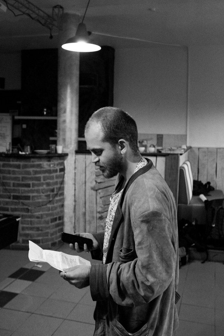 Jonas Galm steht im Backstage und übt seinen Text mit einem Textblatt in der linken Hand.