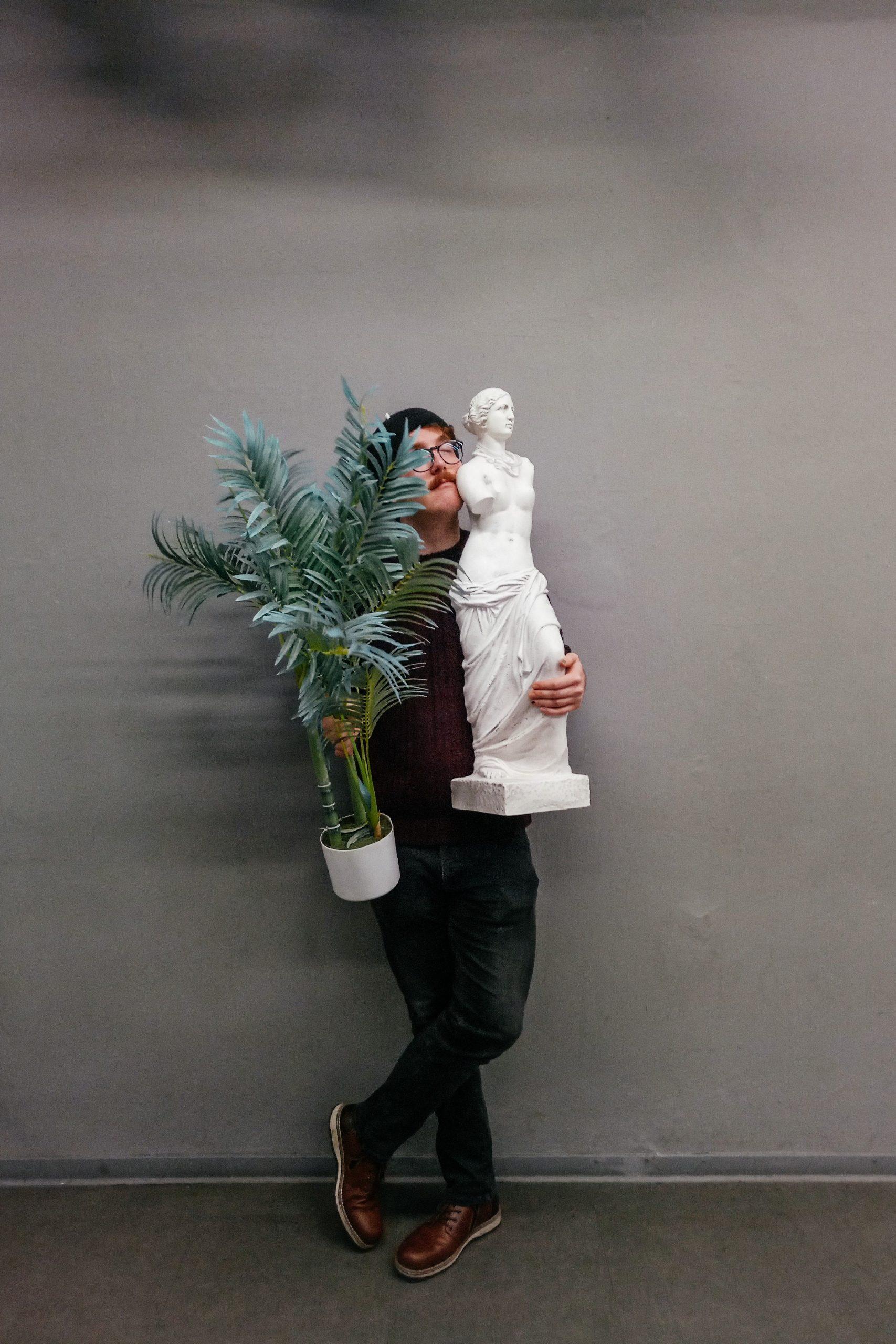 Nils Matzka steht mit verschränkten Beinen da. In der rechten Hand hält er eine Farnpflanze, im linken Arm eine weiße griechische Staute einer Frau.