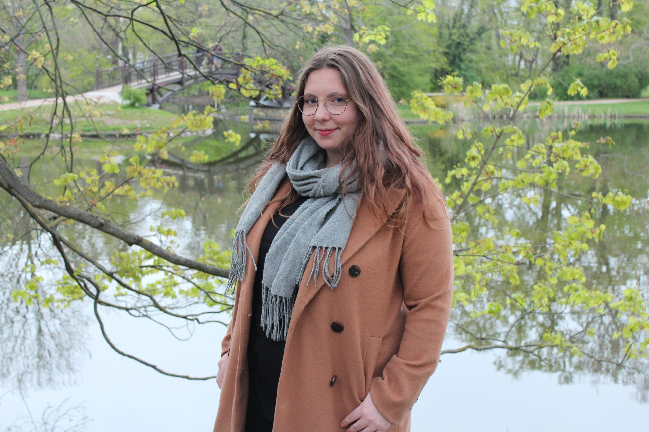Lina Klöpper trägt einen grauen Schal und einen hellbraunen Mantel. Im Hintergrund sieht man den Johannapark